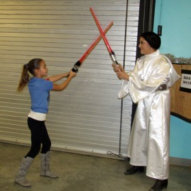 Kendall Courtright, 10, engages in an epic lightsaber battle with Princess Leia (Jess Bernal) on Thursday at the Santa Maria Valley Discovery Museum. (Janene Scully / Noozhawk photo)